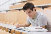 φοιτητής κάθεται διαβάζοντας ένα βιβλίο και λήψη σημειώσεων — Φωτογραφία Αρχείου