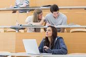Uczniowie siedzący w wykładzie z dziewczyna myśli w laptopie — Zdjęcie stockowe
