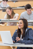 Girl sitting in lecture hall using laptop — Stock Photo