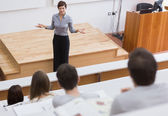 Teacher standing talking to the students — Stock Photo