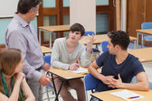 Students sitting talking to the teacher — Stock Photo