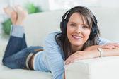 Kobieta słuchania muzyki wyglądający zadowolony na kanapie — Zdjęcie stockowe