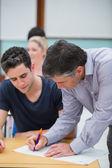 учитель, делая примечание на работе студентов — Стоковое фото