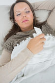 Sleeping woman lying on sofa with a cold — Stock Photo