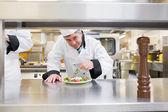 Smiling chef garnishing salad — Stock Photo