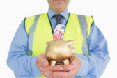 Man in vest holding a piggy-bank — Stock Photo