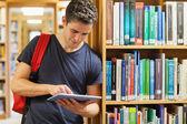 Estudiante apoyado en estantería sosteniendo un tablet pc — Foto de Stock
