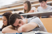 Student sitting at the lecture hall and sleeping — Stok fotoğraf