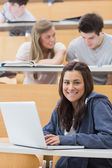 Girl sitting at the lecture hall with laptop — Stock Photo