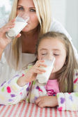 Mother and little girl drinking milk — Stock Photo