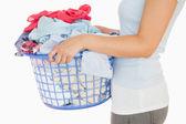 женщина держит корзину переполнен прачечная — Стоковое фото