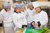 Trainees learning vegetable slicing — Stok fotoğraf