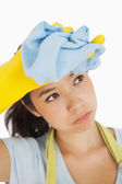 Woman wiping her brow wearing rubber gloves — Stock Photo
