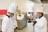 Upset head chef scolding employees — Stock Photo