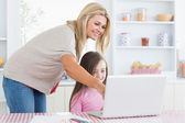 Mother pointing at laptop with daughter — Stock Photo
