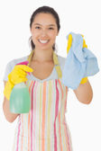 Smiling woman holding up rag and spray bottle — Stock Photo