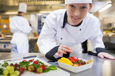 Happy chef preparing fruit salad — Stock Photo