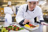 Happy chef preparing fruit salad — Stock Photo