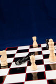 Black queen lying at the chessboard — Stock Photo