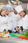 Koch auszubildenden beizubringen, gemüse zu schneiden — Stockfoto
