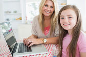 Woman typing at the laptop with daughter — Stok fotoğraf
