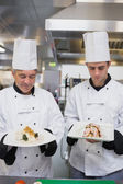 Two cooks proudly presenting their meals — Stock Photo