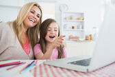 Woman and child sitting at the kitchen table laughing — Stock Photo