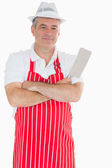 Butcher with arms crossed holding meat cleaver — Stock Photo