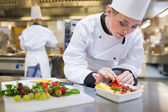 Chef putting a strawberry in the fruit salad — Stockfoto