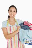 Smiling woman holding laundry basket — Stock Photo