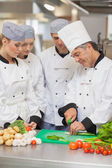 Chef teaching cutting vegetables to three trainees — Stockfoto