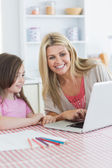 Mother and girl sitting at the kitchen with laptop — Stock Photo