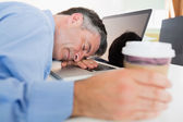 Man sleeping on his laptop while holding coffee — Stock Photo