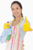 Woman holding cleaning products giving thumbs up — Stock Photo