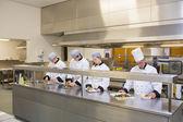 Four Chef's preparing plates — Stock Photo