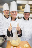 Baker giving thumbs up covered in dough — Stock Photo