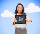 Affärskvinna hålla en tabletpc medan leende visar vagn — Stockfoto