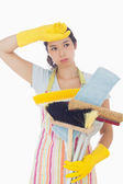 Overworked woman holding cleaning tools — Stock Photo