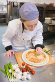 Chef finishing off a pizza — Stock Photo