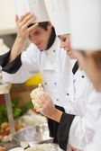 One chef kneading dough while others are watching — Stock Photo