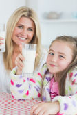 Mother and girl holding up glasses of milk — Stock Photo