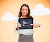 Businesswoman holding a tablet pc showing a shopping symbol — Stock Photo