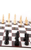 Black and white chess pieces standing at the chessboard — Stock Photo