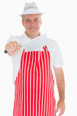 Butcher holding out meat cleaver — Stock Photo