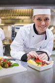 Smiling chef finishing the fruit salad — Stock Photo