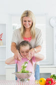 Woman and child mixing salad together — Stock Photo