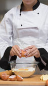Chef cracking egg into bowl of flour — Stock Photo
