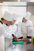 Culinary students learning how to chop vegetables — Stock Photo