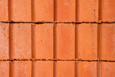 Stack of clay bricks building a wall — Stock Photo