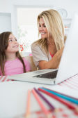 Woman smiling at her daughter by the laptop — Stock Photo
